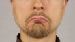 men's lips corners down, expressing sadness, closeup