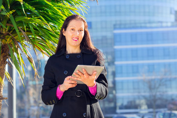 Businesswoman working on digital tablet outdoor over building