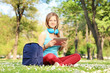 Young female student with headphones and tablet sitting in park