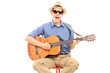 Young man with sunglasses and hat playing on acoustic guitar