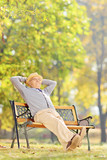 Senior gentleman sitting on bench and relaxing in a park