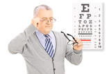 Senior gentleman trying on glasses in front of eyesight test