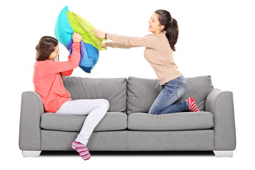 Two young girls having a pillow fight seated on sofa