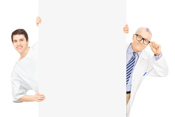 Young male patient and middle aged doctor standing behind panel