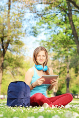 Young female student with headphones and tablet sitting on grass