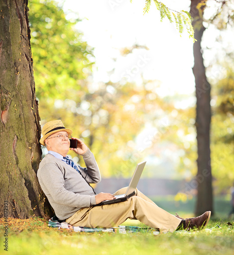 Senior man sitting in a park, talking on a phone and working on