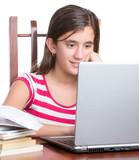 Teenager working on her laptop isolated on white