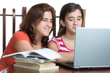 Hispanic teen and her mother working or browsing the web on a la