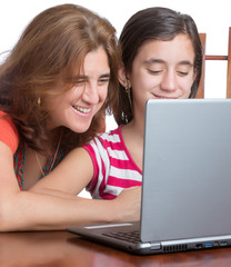 Hispanic teenager and her mother browsing the web