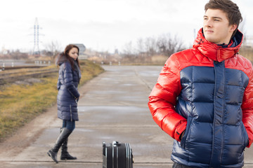 Young couple waiting with their suitcase