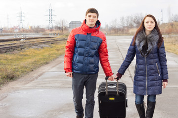 Young man and woman pulling along a suitcase