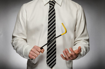 Man wearing tie holding crowbar