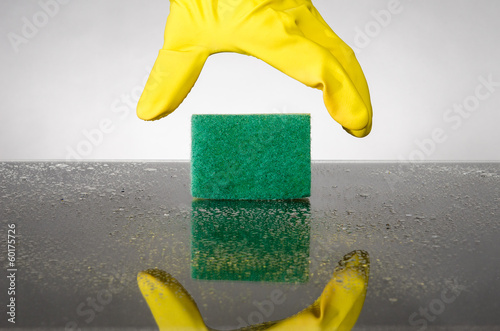 Hand wearing glove reaching for sponge