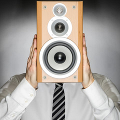 Man wearing tie holding speaker in front of face