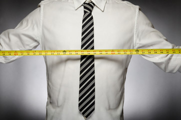 Man wearing tie holding tape measure