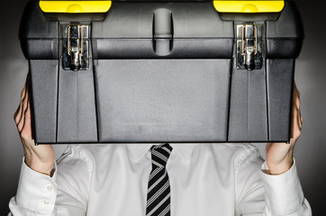 Man wearing tie holding toolbox in front of face