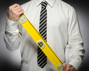Man wearing tie holding level