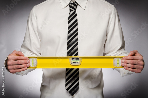 Man wearing tie holding large level