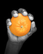 Hand holding an orange - partially monochrome, low key