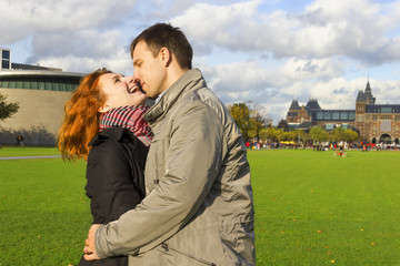 Outdoor happy couple in love, Museum Plein, autumn Amsterdam bac