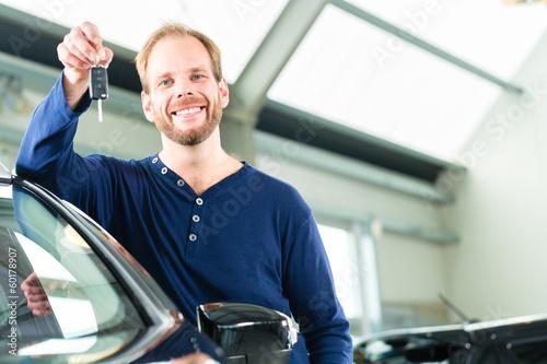 Kunde mit Autoschlüssel vor Auto in Autohaus