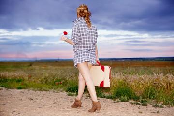joven con maleta y flor en busca de nuevo camino