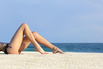 Beautiful woman legs resting on the beach sunbathing