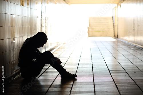Leinwanddruck Bild Teenager depressed sitting inside a dirty tunnel