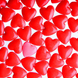 Pink heart between a pile of red hearts. Candy Hearts background