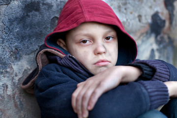 homeless boy leaned against the wall