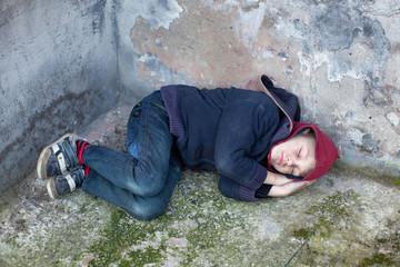 homeless boy sleeps under the wall