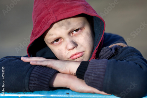 dramatic portrait of a little homeless boy