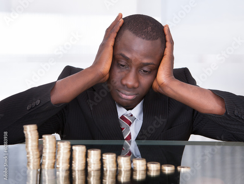 Worried Businessman Looking At Coins