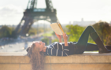 Girl reading a book in Paris on a sunny day