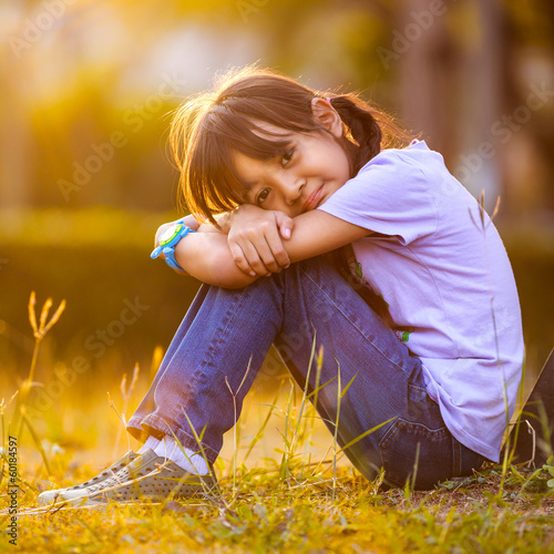 Happy girl sitting on grass in garden