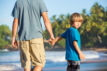 Happy father and son walking together on the beach, carefree hap