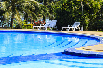 luxury swimming pool with sundeck white close up in tropical gar