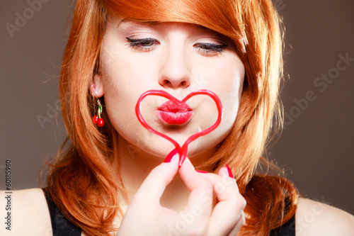 Redhaired girl with red heart love blowing kiss. Valentines day.