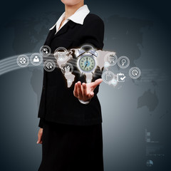 Business woman showing alarm clock and icon web symbol on hand