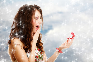 Surprised girl with red gift box with engagement ring. Winter.
