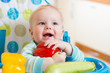 baby with vegetables sitting in chair on kitchen