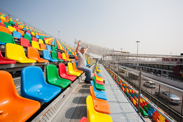 Man with hands up in the seats for spectators