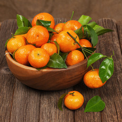Fresh tangerines with leaves in bowl on wooden table.
