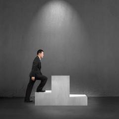 Businessman climbing on podium with spot lighting