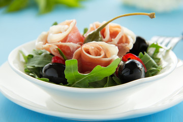 Salad with arugula, prosciutto and olives.