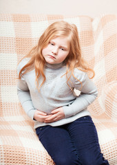 child with stomach ache in sofa