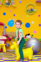 happy kid riding a toy in kindergarten