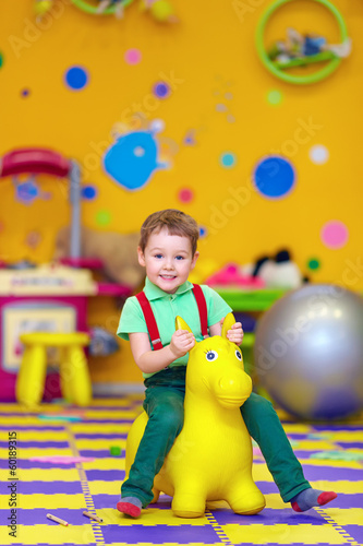happy kid riding a toy in kindergarten