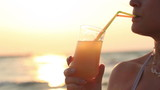 Woman sipping a refreshing cocktail at sunset