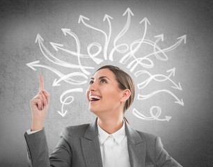 Happy, young businesswoman looking at many twisted arrows on the